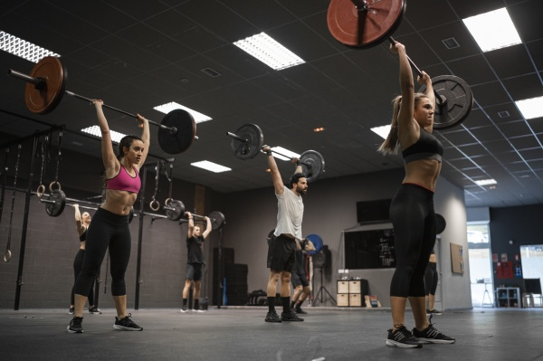 athletes lifting barbell while exercising in