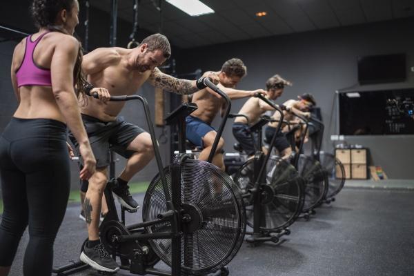 athletes sitting on bike while exercising