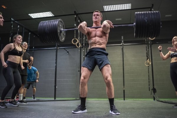 athlete cheering man picking barbell up