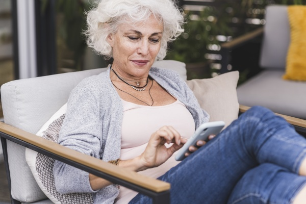 mature woman texting messaging while sitting