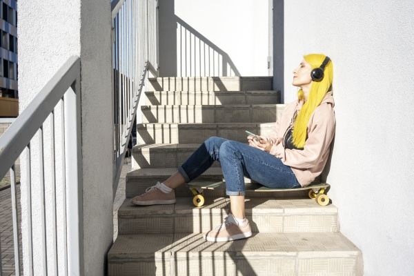 young woman listening music through headphone