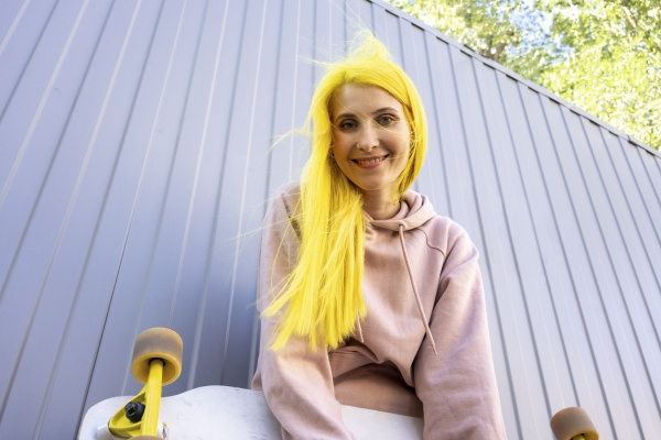 smiling dyed yellow hair woman standing