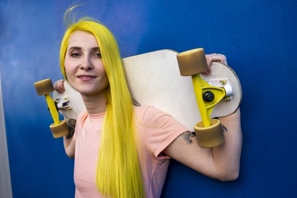 woman holding skateboard standing against blue