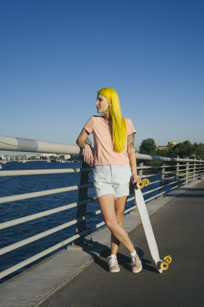 young woman standing on bridge looking