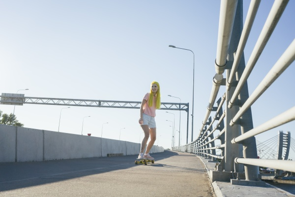 young woman skateboarding on bridge against