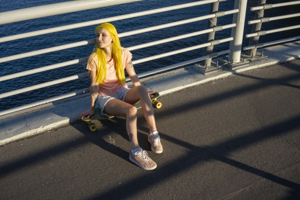 young woman sitting on skateboard against