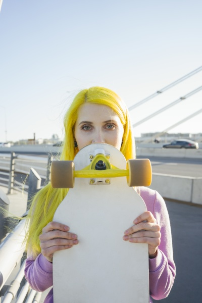 young woman covering face with skateboard