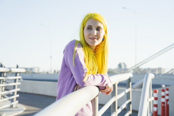 hipster female leaning on railing while
