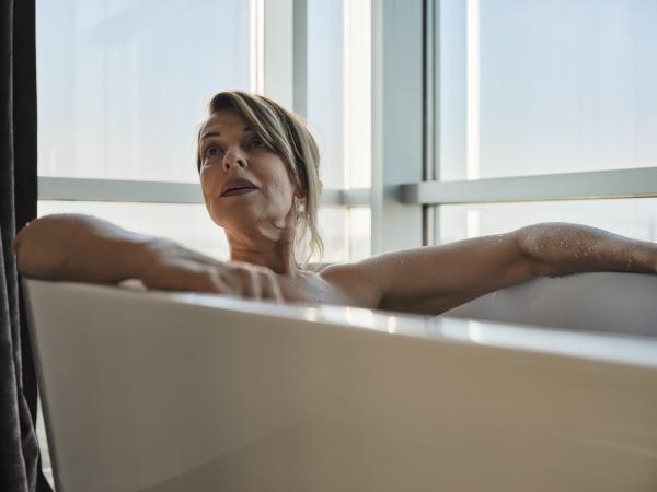 blond senior woman taking bath in