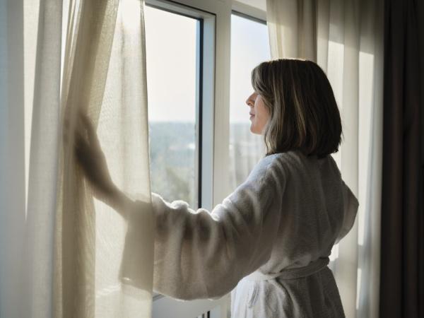 blond senior woman opening white curtain