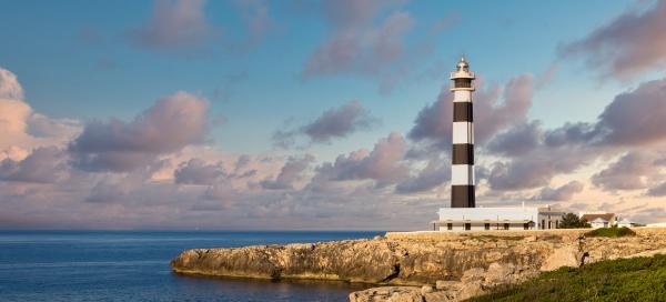 scenic artrutx lighthouse at sunset in