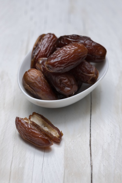 dried dates on white wooden background