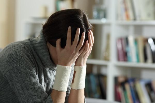 sad woman with bandages on wrists