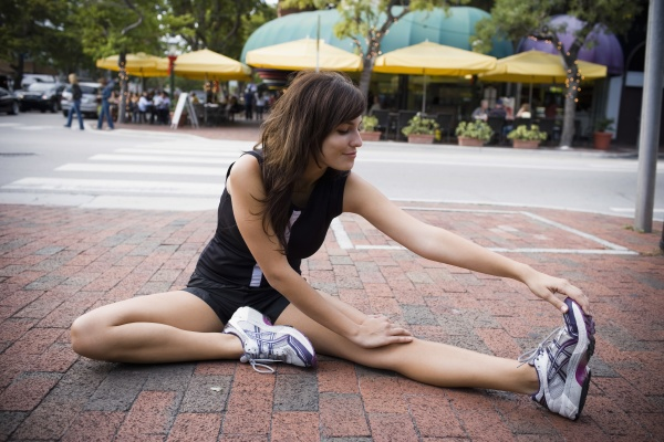 young woman stretching with physical trainer