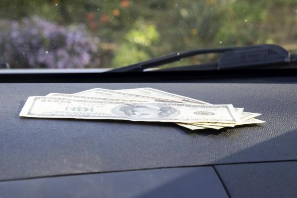 dollars on a car dashboard under