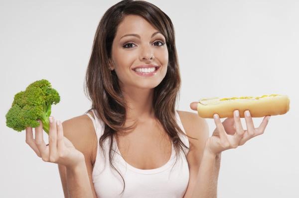 woman choosing between broccoli and a
