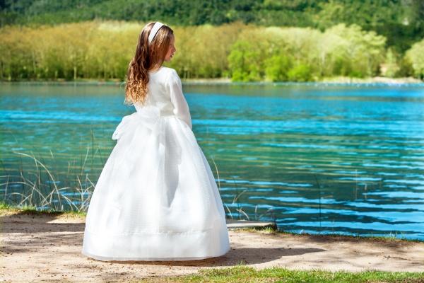 sweet girl in communion dress outdoors