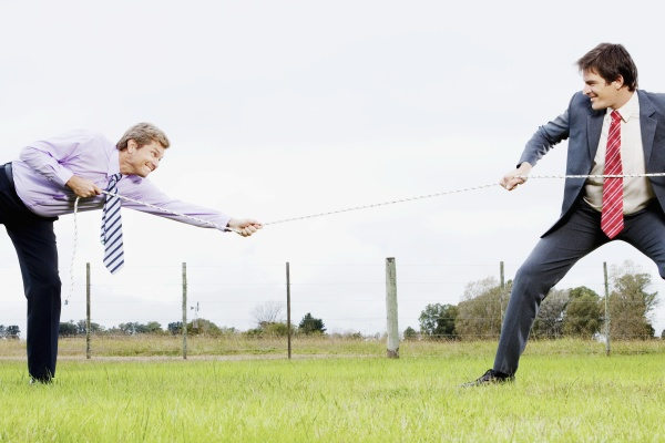 business colleagues playing tug of war