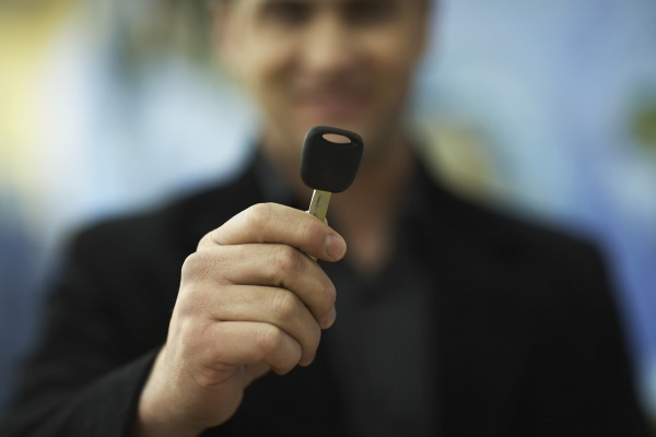 young man holding a car key