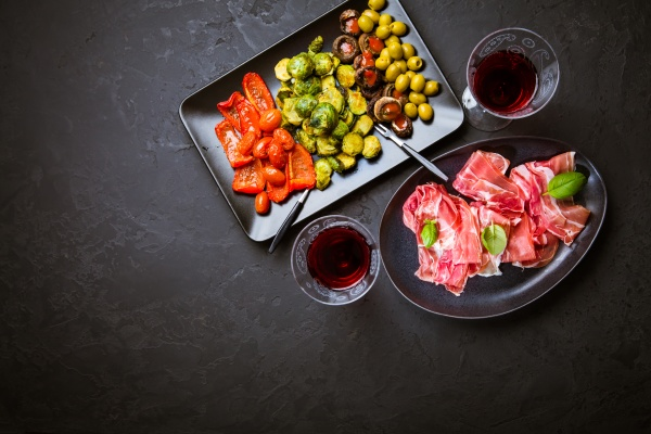 prosciutto with different appetizers with glass