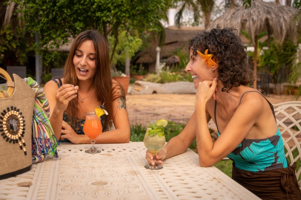 two laughing brunettes sit drinking cocktails