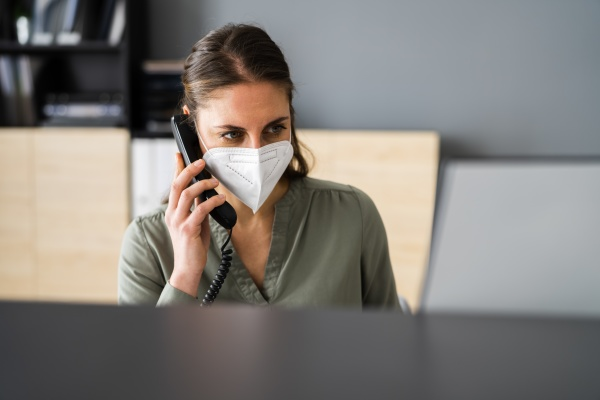 receptionist on phone wearing face mask