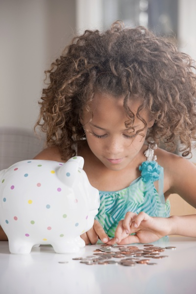 girl with piggy bank counting coins