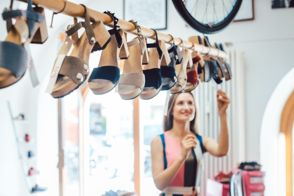 woman looking at shoes dangling from