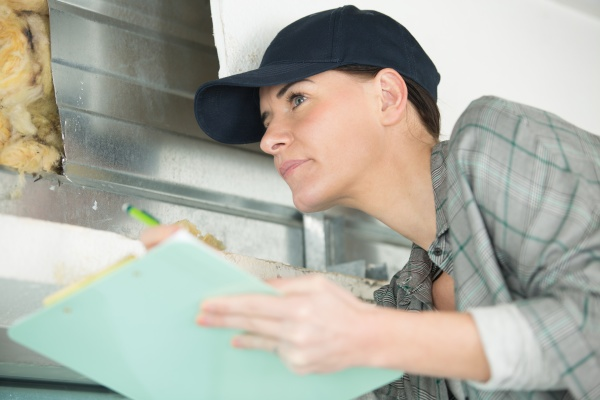 female contractor on site holding clipboard