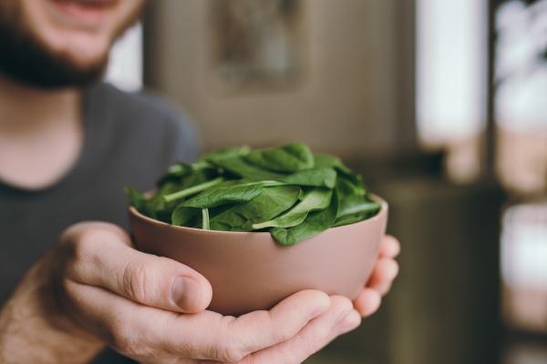 man holding fresh green salad leaves