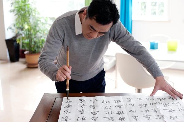 an elderly man practicing calligraphy
