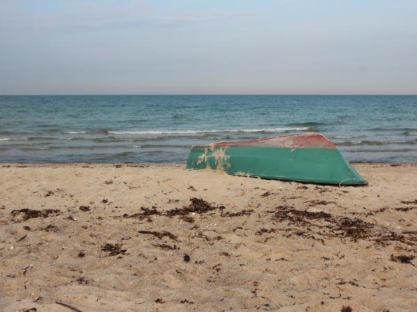 green rowing boat upside down on