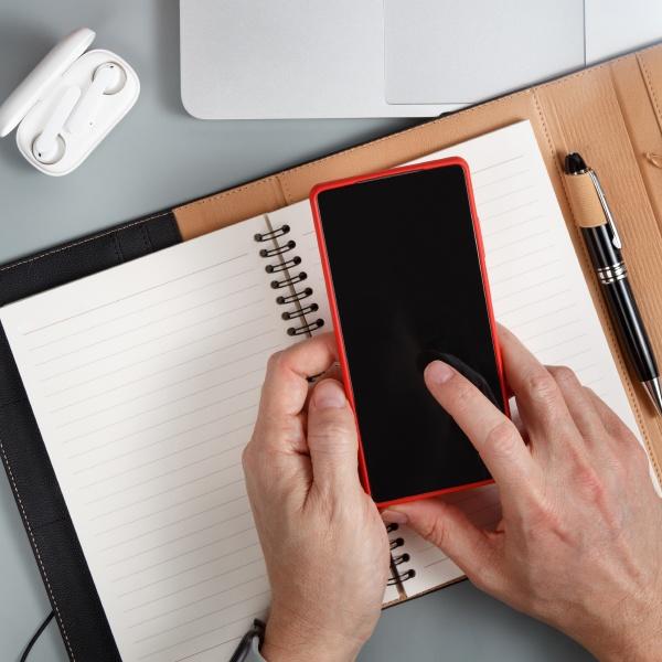 man writing in agenda and using