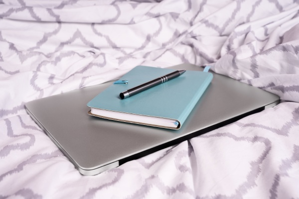 notepad and pen on top of