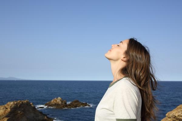 woman breathing fresh air alone on