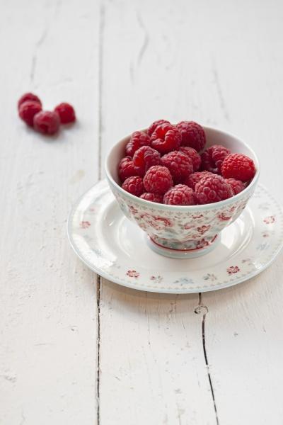 fresh raspberries in porcelain bowl