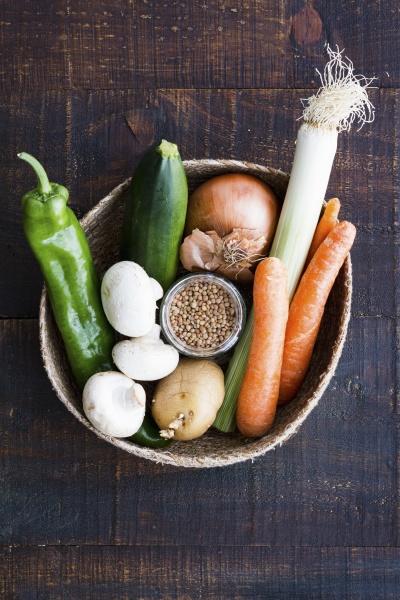 a basket with carrots mushrooms leek