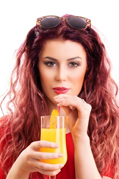 beautiful redhead young woman drinking orange