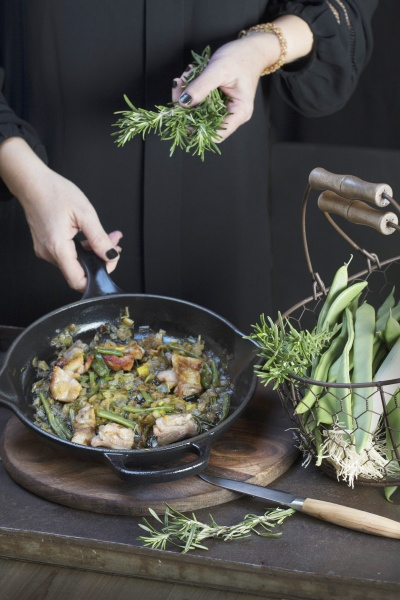 putting rosemary to pan with cooking