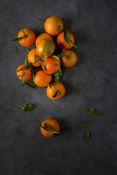 mandarins with leaves on a grey