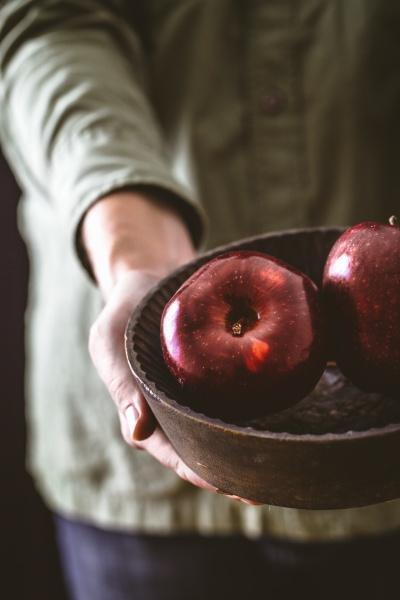 hands holding a wooden bowl with