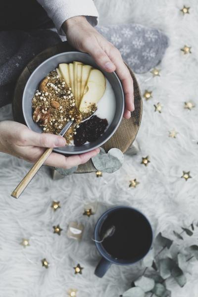 hands taking healthy breakfast bowl