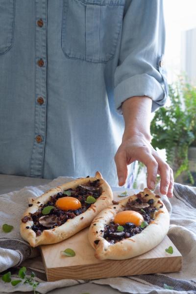 hand takes freshly prepared kachapuri with