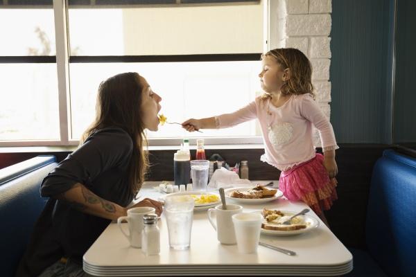 toddler daughter feeding mother in diner