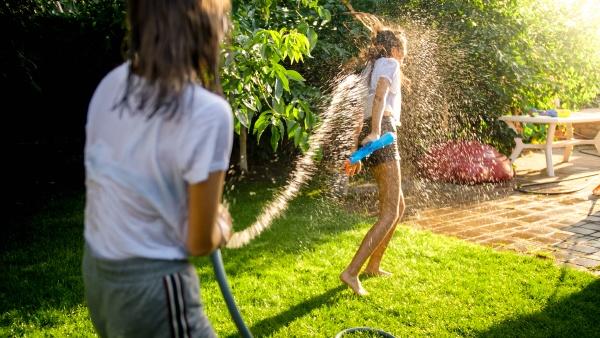 two teenage girls playing water fight