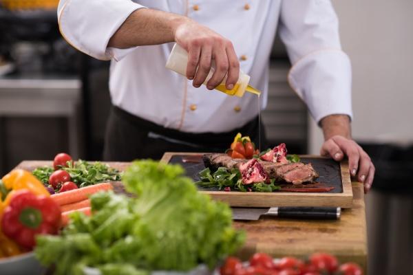 chef finishing steak meat plate