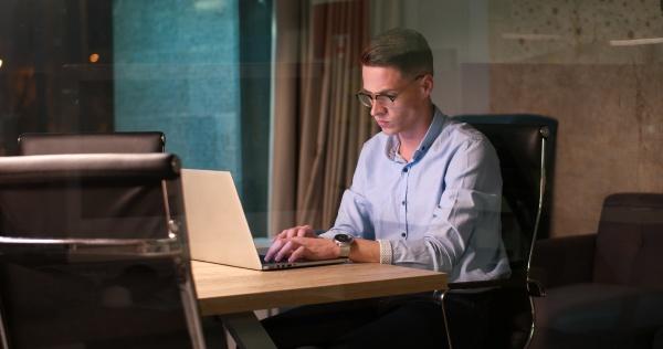 man working on laptop in dark