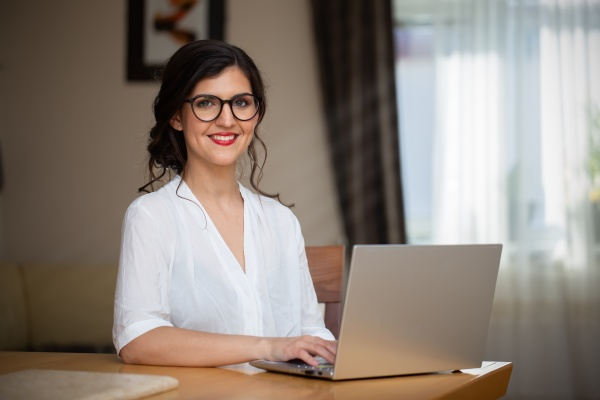 happy businesswoman with glasses working from