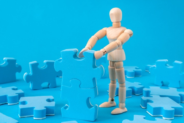 wooden man assembling jigsaw puzzle
