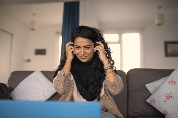 smiling woman with headphones working from